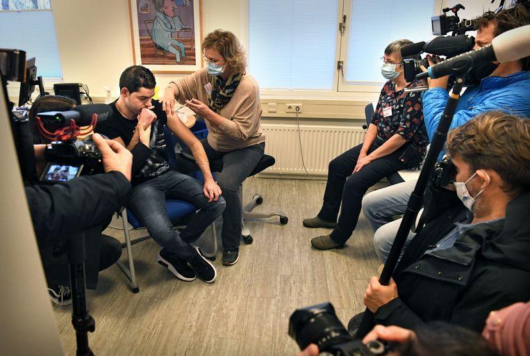 De eerste bewoner van gehandicaptenzorginstelling Middin wordt onder belangstelling van de pers gevaccineerd.  Beeld Marcel van den Bergh / de Volkskrant