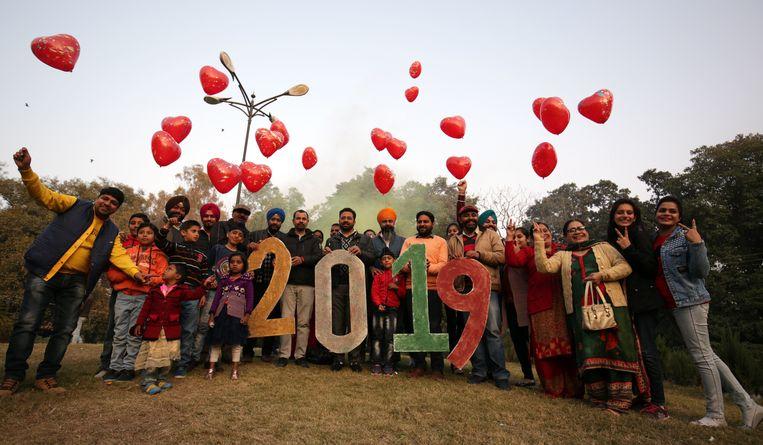 In het Indiase Amritsar nemen buurtbewoners foto's van elkaar bij de nieuwjaarsfestiviteiten.  Beeld EPA