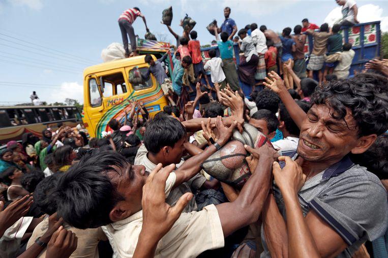 Rohingya-vluchtelingen vechten om een deel van de uitgedeelde hulpgoederen in Bangladesh te bemachtigen. Beeld REUTERS