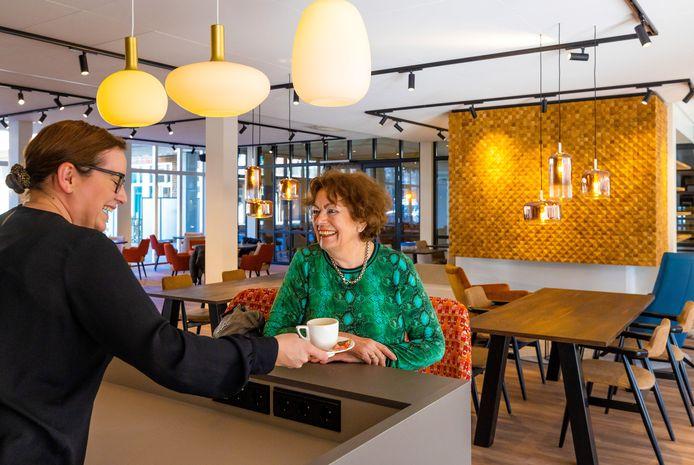 De gordijnen en planten ontbreken nog, maar verder is het restaurant van Residentie Moller in Waalwijk klaar. Bewoonster Jeanette Struijk krijgt van hostess Charlotte Bakker het allereerste kopje koffie.