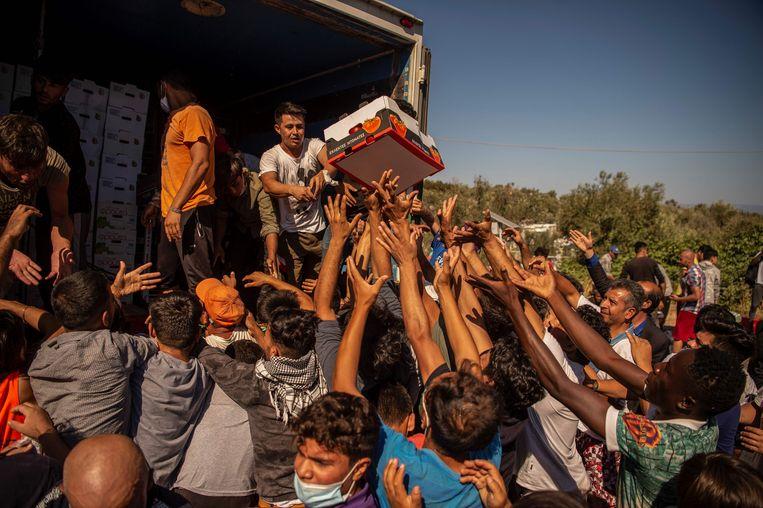 Migranten op het Griekse eiland Lesbos bij de voedseldistributie, een dag nadat kamp Moria door brand is verwoest. Beeld AFP