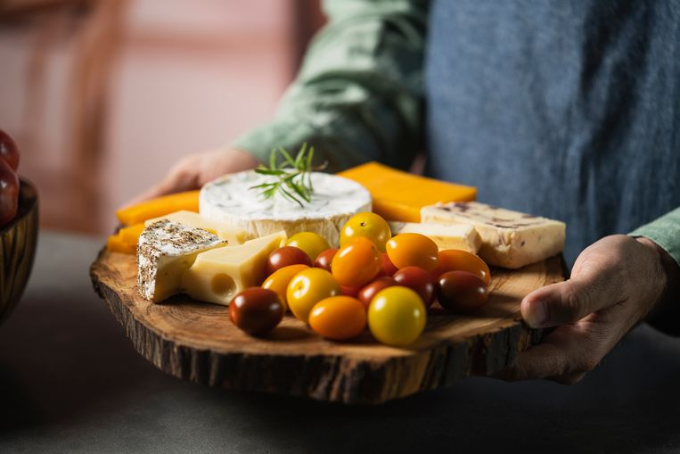 A man with a jeans apron and a green shirt with an assortment cheese and tomatoes board Beeld Getty Images