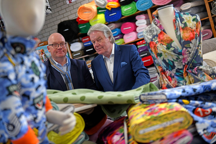 """Oprichter Harry van der Molen (rechts) en zijn zoon Olaf tussen de lappen stof in hun zaak. """"Alleen van modestoffen kun je niet meer bestaan in deze tijd."""""""