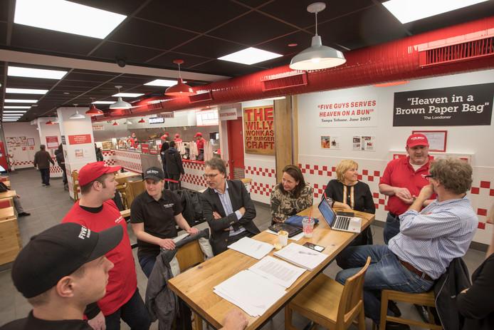 Staf Depla (midden) op bezoek bij de fastfoodzaak Five Guys  aan de Markt in Eindhoven. De wethouder bezoekt regelmatig bedrijven die ook mensen met achterstand op arbeidsmarkt aannemen.