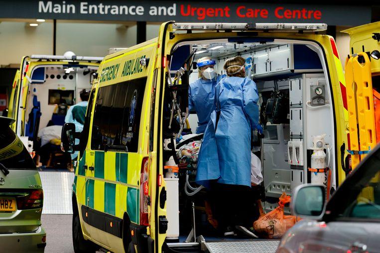 Zorgmedewerkers met coronapatiënten in ambulances aan een ziekenhuis in Londen. Beeld AFP
