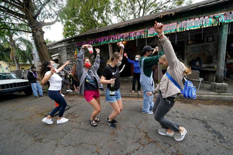Aanhangers van Joe Biden  in New Orleans dansen zaterdag van vreugde nadat bekend is geworden dat Biden genoeg kiesmannen heeft binnengehaald om president te worden.  Beeld AP