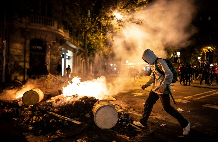 Een man gooit een ton op een door de protesterende Catalanen aangestoken vuur op Rambla de Catalunya in Barcelona. Wat begon als een rustige demonstratie eindigde in een veldslag tussen politie en demonstranten.  Beeld Freek van den Bergh