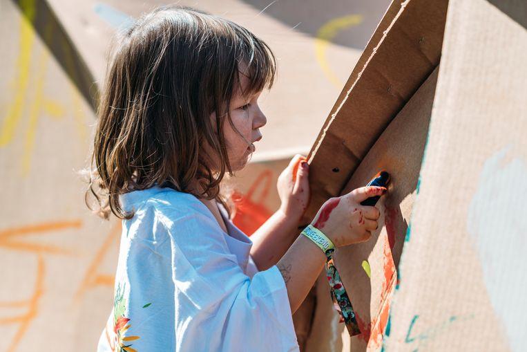 Kinderen beschilderen eerst de kartonnen tent waar ze 's avonds in slapen. Beeld Eva Beeusaert
