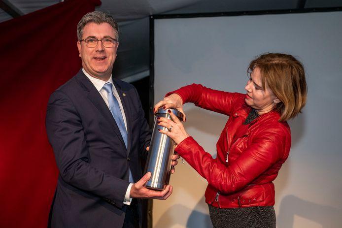 Gedeputeerde Van der Maas (links) en minister Van Nieuwenhuizen (Infrastructuur en Waterstaat) met de tijdcapsule die in de Tractaatweg wordt gestopt.