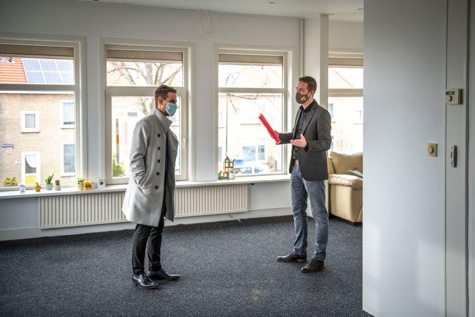 Makelaar Rogier Voorzaat (rechts) geeft Mitchell van Doorn een rondleiding in de bovenwoning aan de Anjelierenlaan in Vlissingen.