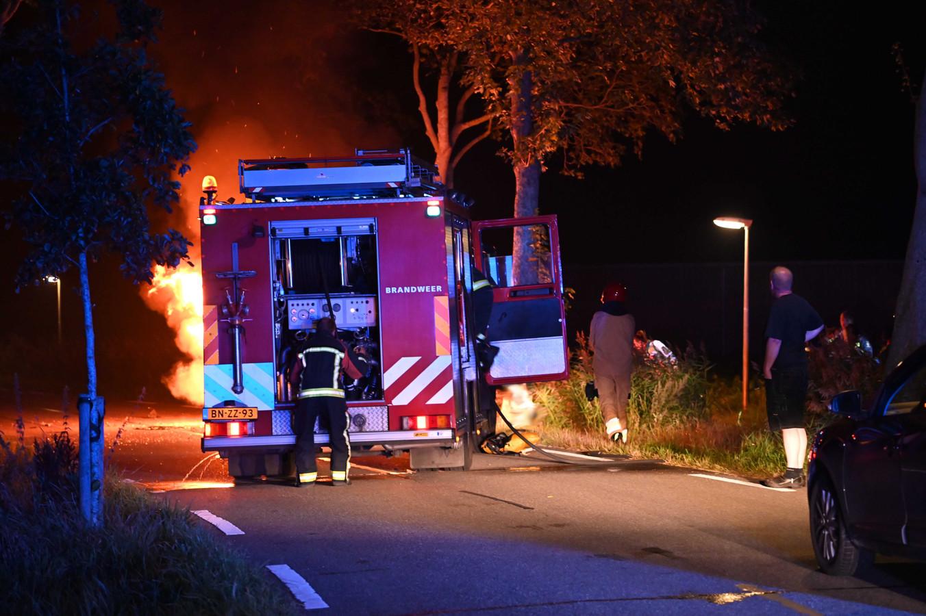De brandweer blust een brandende auto.