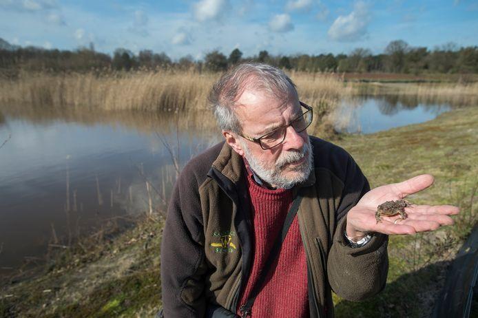 Ron Felix, een van de vele onderzoekers in natuurgebied De Kaaistoep, aan de rand van een poel. Op zijn hand een pad.
