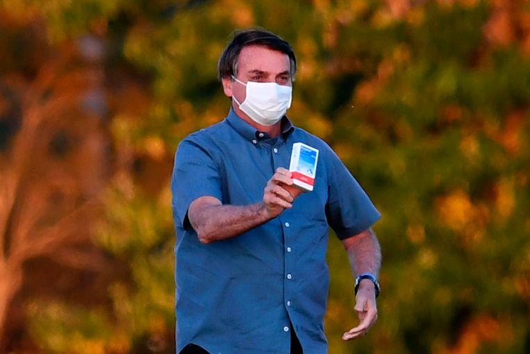 De Braziliaanse president Bolsonaro toont een doosje met hydroxychloroquine.  Beeld AFP