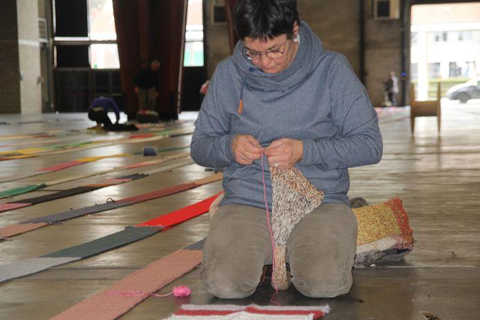 Een ouder breit nog enkele stukken sjaal aan elkaar.
