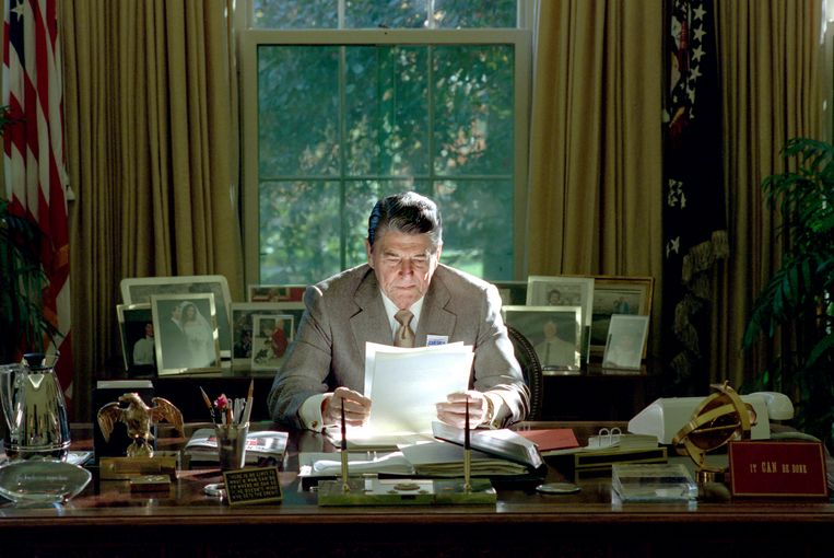 """President Reagan  in The Oval Office, 26 oktober 1988. Rechtsonder het bordje met de tekst ,,It can be done"""".  Beeld National Archive"""