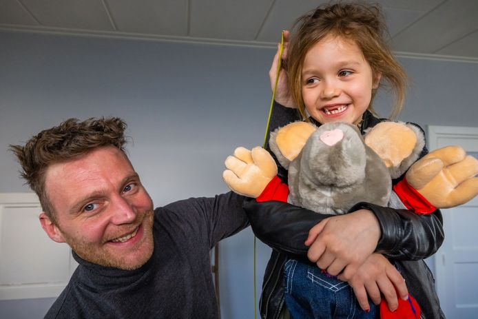 Rutger van Happen meet kleding op bij zijn nichtje Babette de Ruijter (6). Zij houdt de oude mascotte van het kinderkledingbedrijf Villa Happ Rat Arjo vast.