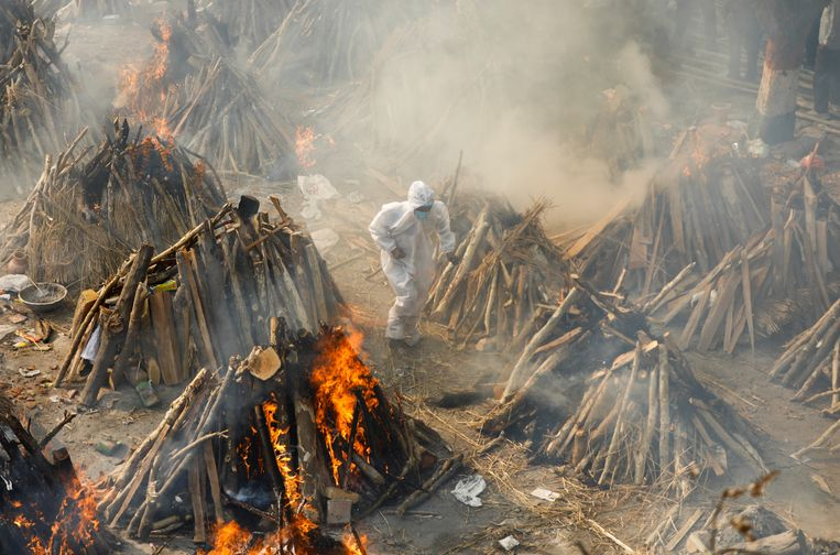 Een man in een beschermend pak loopt tussen brandstapels van coronadoden door bij een massacrematie maandag in Delhi. Beeld Reuters