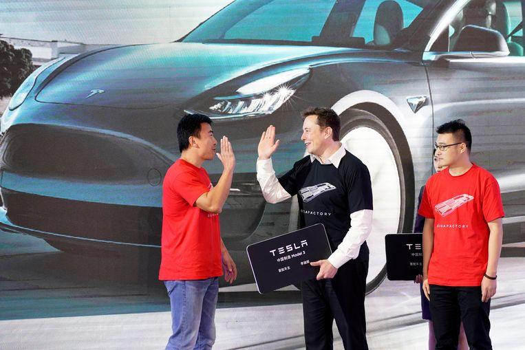 Tesla-baas Elon Musk (midden) op een podium in zijn fabriek in Shanghai, China. Als gevolg van de handelsoorlog tussen de VS en China heeft hij die fabriek versneld laten bouwen. Beeld Reuters