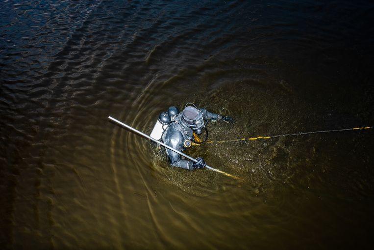 Een duiker zoekt naar een wapen dat is gebruikt bij de liquidatie van Serdar Ay in oktober bij Hoekenes. Beeld Nosh Neneh