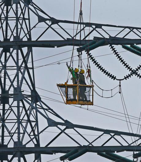 Spectaculair! Monteurs hangen vanuit mandje onder helikopter vlaggetjes aan stroomdraden