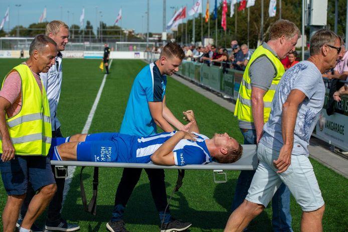 Gert-Jan van Leiden verlaat op een brancard het veld nadat zijn rechterschouder tijdens het duel met Ter Leede (3-2) uit de kom is geschoten. In het midden Ruben Deij, fysiotherapeut van Hoek.