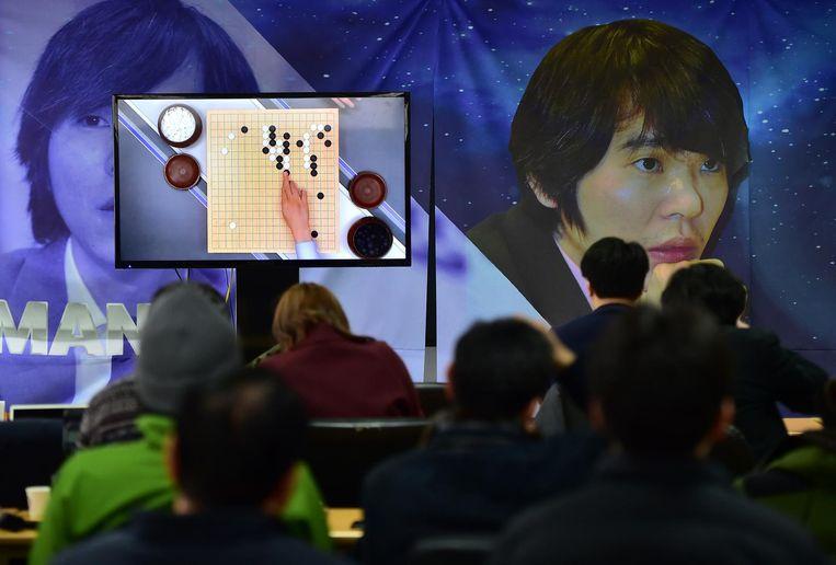 Via een scherm volgen fans de partij die het programma AlphaGo won van grootmeester Lee Sedong. Beeld afp