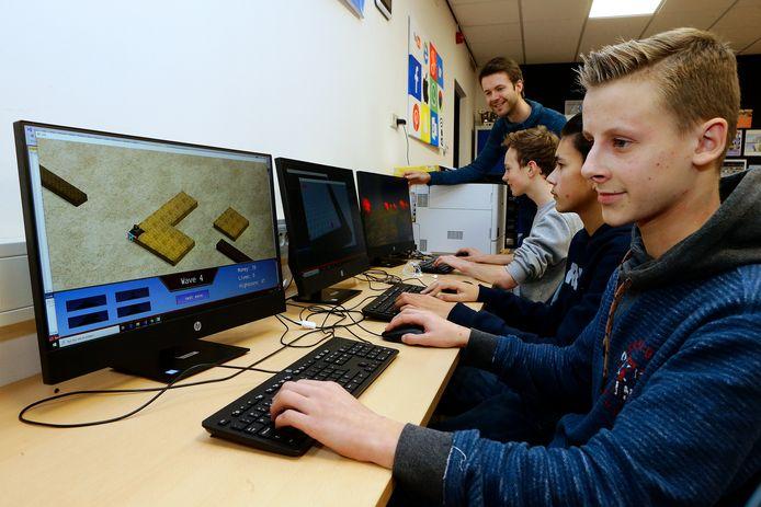Lukas Kraaij bouwt een 'virtuele weg'. Achter hem klasgenoten Aron van der Steen, Martijn Bot en docent David van Vugt.