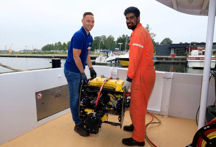 Nick van den Aarssen (links) van inspectiebedrijf Asset.Insight showt in Terneuzen de onderwaterrobot met Gurteshwar Mander van het Indiase bedrijf Planys dat het high tech-apparaat op de markt brengt.