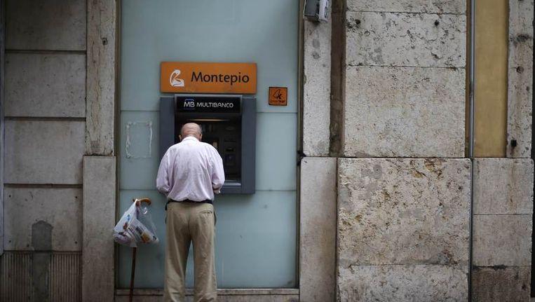 Een man pint geld in Lissabon, Beeld reuters
