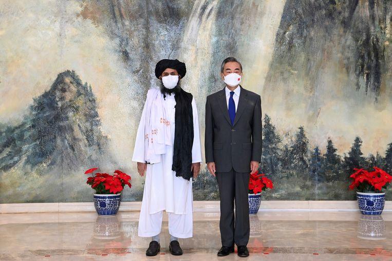 Mede-oprichter van de Taliban mullah Abdul Ghani Baradar poseert met de Chinese minister van Buitenlandse Zaken Wang Yi tijdens een bezoek aan Beijing, eind juli.  Beeld AP