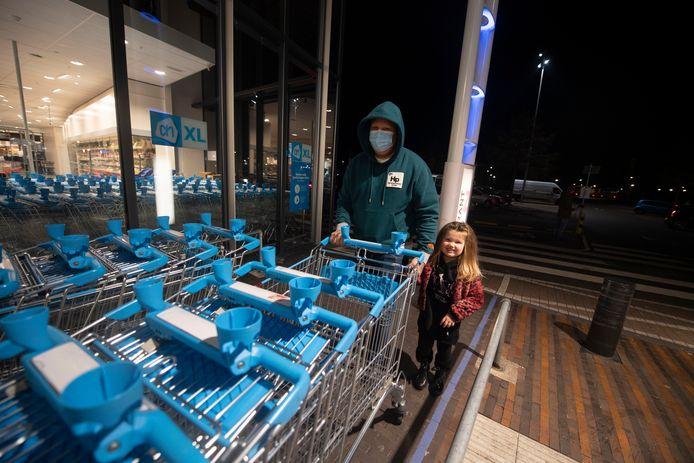 De avondklok gaat in. Bij de AH XL in Enschede gaan Kaan en zijn dochtertje Richelle nog snel de laatste boodschappen halen.