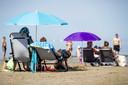 Badgasten op het strand. Nu er een periode met zonnig en heet zomerweer is aangebroken, zijn mensen op zoek naar verkoeling.