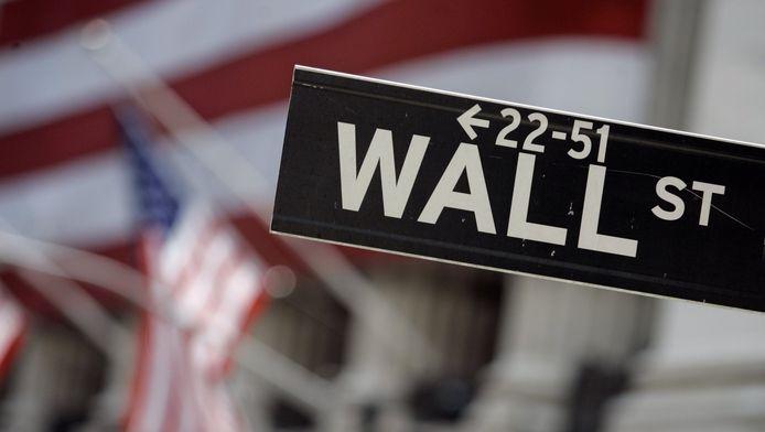 Het staatnaambordje van Wall Street, met op de achtergrond de Amerikaanse vlaggen aan de New York Stock Exchange.
