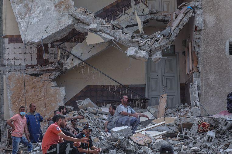 Palestijnse civiele diensten meten de schade op, na een Israëlische luchtaanval op Gaza City.  Beeld EPA