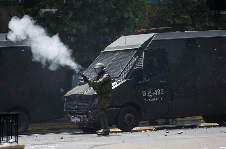 Een medewerker van de veiligheidsdiensten vuurt een wapen af tijdens de betoging.
