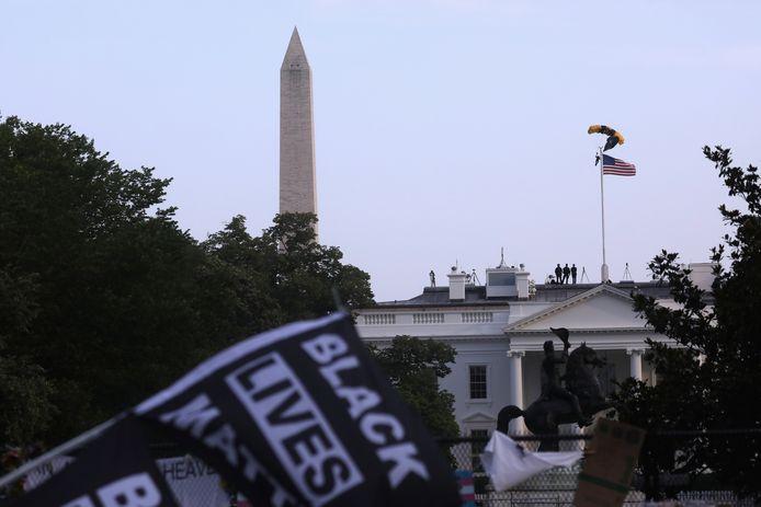 Parachutisten vliegen over het Witte Huis heen, terwijl Black Lives Matter-vlaggen worden gezwaaid voorafgaande aan Trumps toespraak.
