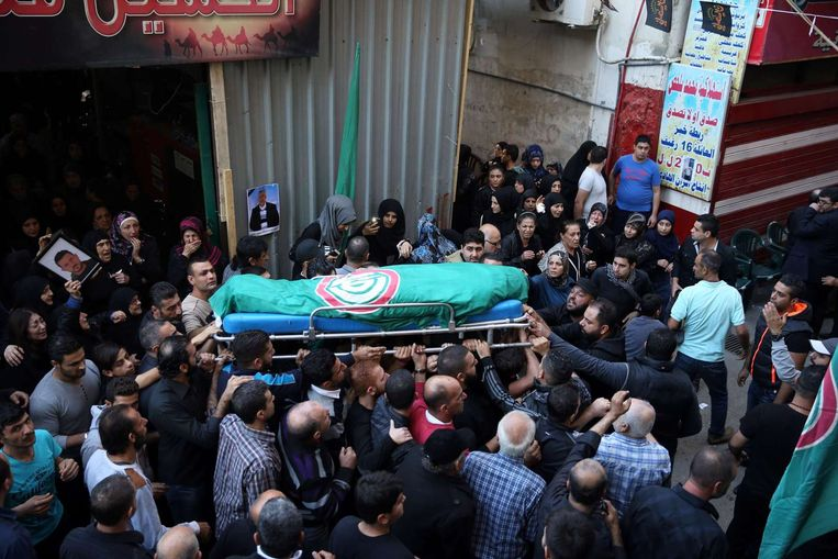 Mourners carry the body of Samer Huhu during his funeral in the southern suburb of the capital Beirut. Beeld AFP