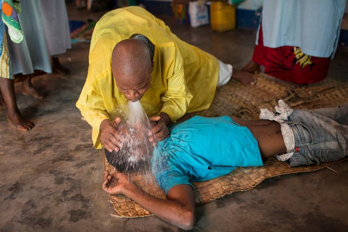 Een priester voert een genezingsritueel uit in Kinshasa. Congolese kerken verdienen veel geld aan duiveluitdrijvingen.