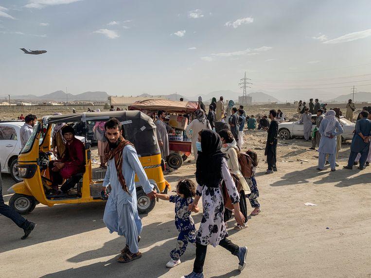 Afghanen bij het vliegveld van Kabul, op 21 augustus dit jaar, een week na de machtsovername door de Taliban. Beeld Jim Huylebroek / ANP