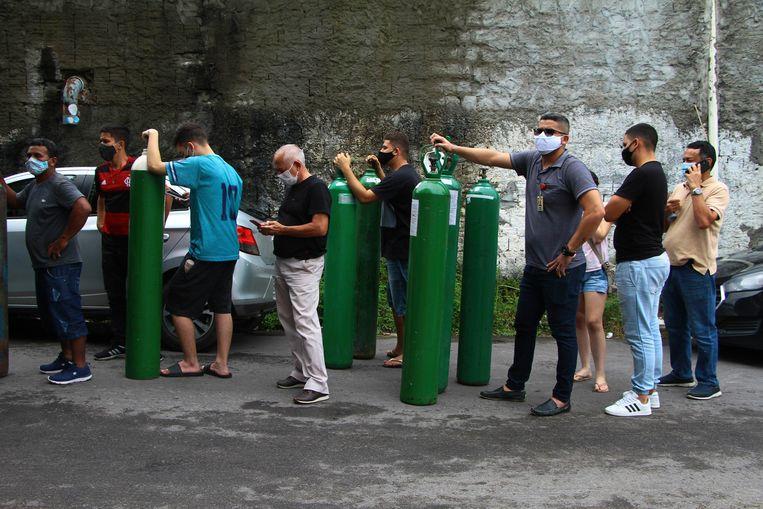 Familieleden van covid-patiënten proberen lege zuurstofflessen te laten vullen bij een fabriek in Manaus, om die weer naar het ziekenhuis te brengen. Er is een tekort aan zuurstof in de ziekenhuizen. Beeld AP