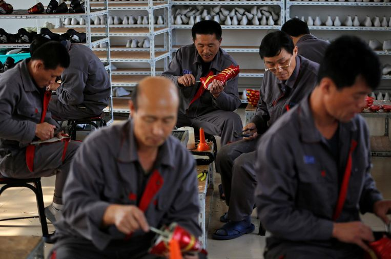 Noord-Koreaanse arbeiders maken sportschoenen in een tijdelijke fabriek even buiten Dadong. Beeld Reuters