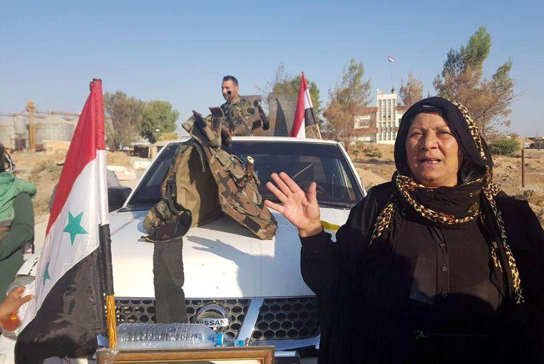 Een Syrische vrouw verwelkomt een soldaat van het Syrische leger in een pick-up truck bij de plaats Tel Tamer in Noordoost-Syrië. Beeld REUTERS