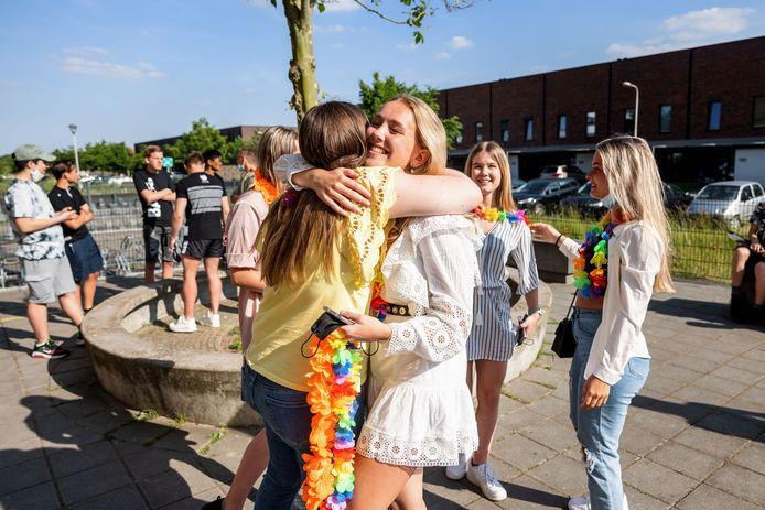 Leerlingen vliegen elkaar in de armen als ze elkaar zien op het schoolplein van het Reeshofcollege.