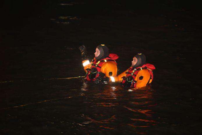 Duikers van de brandweer zoeken het water af.