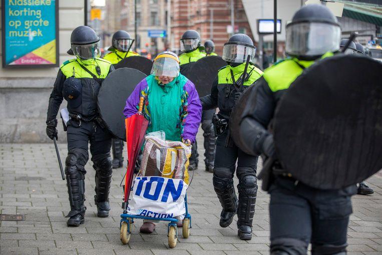 De politie en de Mobiele Eenheid hebben zondagmiddag in Amsterdam het Museumplein schoongeveegd. Honderden mensen hadden zich daar verzameld om te demonstreren tegen de coronaregels.  Er werd met vuurwerk naar de agenten gegooid. Rond 15.30 uur was het Museumplein leeg, demonstranten houden zich nog wel in omliggende straten op. De actievoerders worden door de ME de Van Baerlestraat door gedreven.  Zondagmiddag werd er al een noodbevel afgekondigd, maar daar trokken velen zich niets van aan. Daarop werd besloten in te grijpen. âĞOndanks de vele waarschuwingen van gemeente en politie en het afgekondigde noodbevel gaan de demonstranten op het Museumplein niet uiteen. De politie treedt nu op volgens draaiboek. Na meerdere waarschuwingen via versterkt geluid is de waterwerper ingezetâĝ, zo liet de gemeente weten.  Een oudere vrouw met een rollator die door agenten van het plein werd gehaald gooide een groen poeder naar de agent die daardoor onder het poeder kwam te zitten. De oudere vrouw werd vervolgens aangehouden. Beeld Michel van Bergen