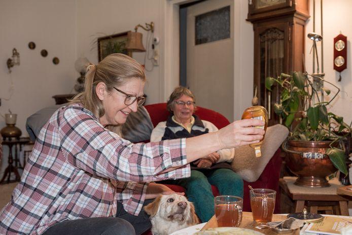 Joke Davenne (links) laat nooit iemand stikken. Hier drinkt ze een kopje thee met buurvrouw Inez ten Rouwelaar, die een blessure aan haar linkerarm heeft en waar Joke af en toe spontaan even helpt.