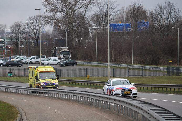 Het slachtoffer van het bedrijfsongeval wordt onder politiebegeleiding naar het ziekenhuis vervoerd.
