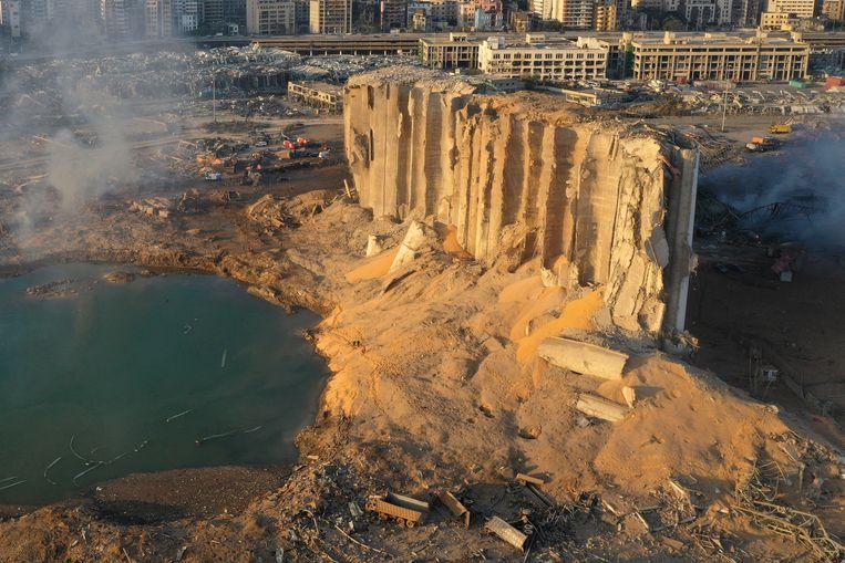 Een deel van de silo in de haven van Beiroet waar de explosieve stof lag opgeslagen staat nog overeind. Op de achtergrond de verwoeste stad.  Beeld AP