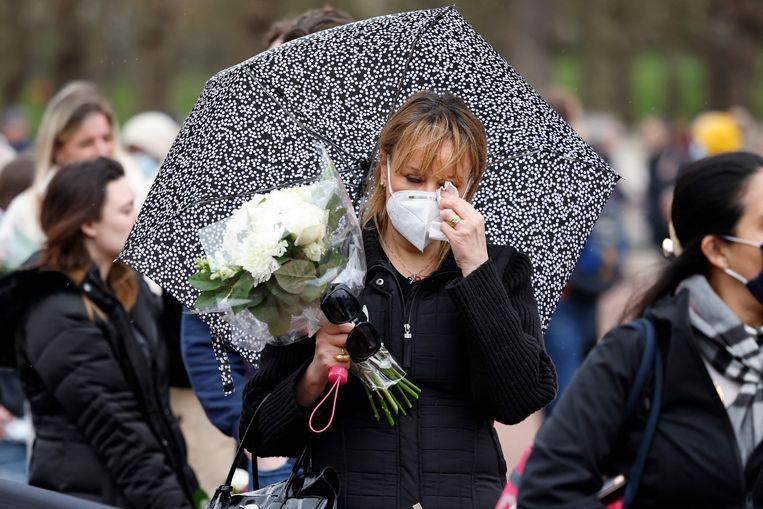 Mensen wachten voor Buckingham Palace om bloemen te kunnen leggen. Beeld AFP