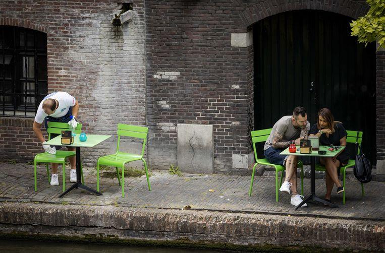 Een ober maakt een stoel schoon op het terras langs de Oude Gracht. In de horeca werken veel mensen op flexibele basis. Beeld ANP, Robin van Lonkhuijsen